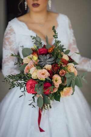 bride in a white dress holding a bouquet of flowers and greenery Banque d'images - 132059209