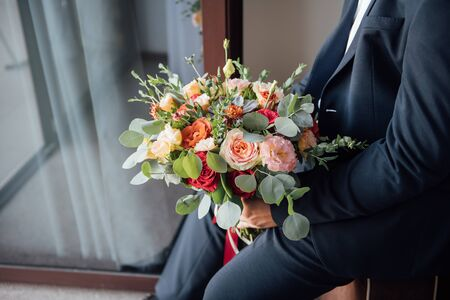 the groom waits for the bride and holds in hands a beautiful wedding bouquet