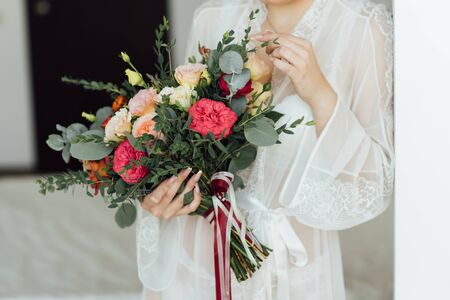 bride in a white dress holding a bouquet of flowers and greenery Banque d'images - 132057489