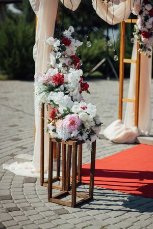 Decoration wedding arch with white and pink flowers on a green natural background.
