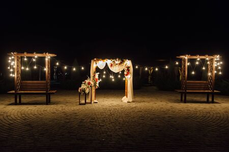 night wedding ceremony. A garland of light bulbs. candles in glass flasks in the evening.