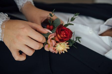 Hands of bride outdoors. Bride corrects boutonniere on grooms wedding jacket