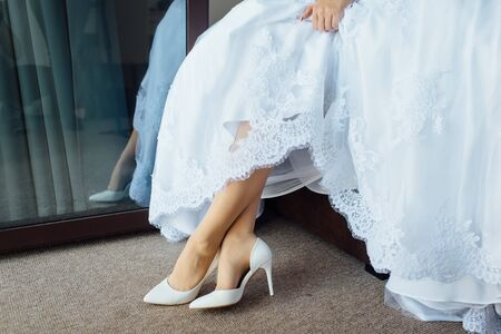 beautiful bride in a dress puts on white shoes Archivio Fotografico