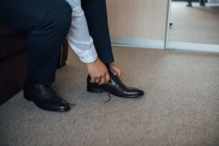 Business man tying shoe laces on the floor. Close-up