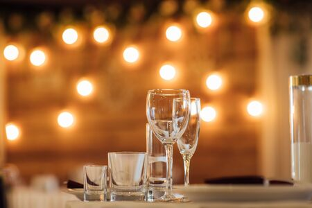 Glasses, flower fork, knife served for dinner in restaurant with cozy interior Archivio Fotografico