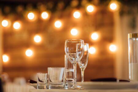 Glasses, flower fork, knife served for dinner in restaurant with cozy interior 版權商用圖片