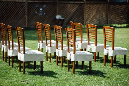 rows of chairs in white capes for guests at a wedding ceremony event outside Stock Photo