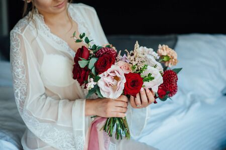 A bride in a white dress is holding a beautiful wedding bouquet.
