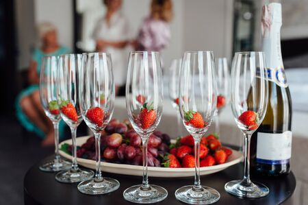 a row of classic glasses with strawberries ready to pour champagne from a bottle. Sparkling wine glasses ready for toasting Stock Photo