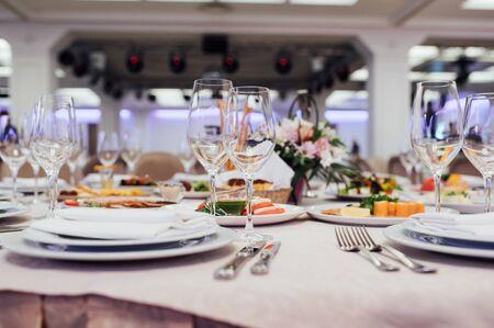 Glasses, flower fork, knife served for dinner in restaurant with cozy interior Stock fotó