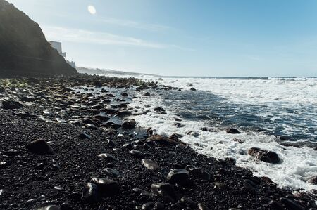 White foamy breaking waves on the beach with black volcanic sand on Tenerife.