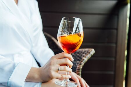 sexy woman holding a glass with aperol cocktail and smiling in the sun