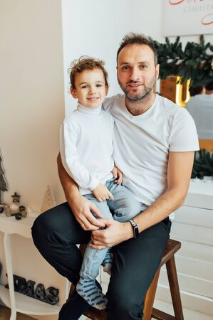 happy father hugs his sons. Photo taken in an apartment with a Christmas tree