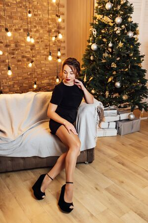 Christmas fashion photo of beautiful girl in black dress posing near New Year tree with presents.