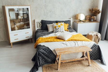 Comfortable, big, wooden bed with linen, pillows and blanket, nightstand beside and round mirror.
