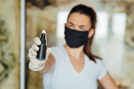 A girl in a protective mask, glasses and gloves spray an antiseptic to prevent infection. 写真素材
