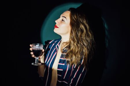 girl on green background with a glass of red drink wine smoke looks aside 写真素材