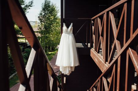 Elegant wedding dress hanging on a wooden railing outside
