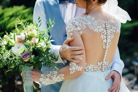 Cheerful newlyweds are hugging at their wedding and covering their face with a wedding bouquet