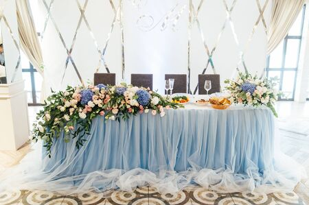 Luxurious wedding presidium in white with blue elements. Groom and bride 's table decorated with beautiful flowers, candles a stylish white background 写真素材