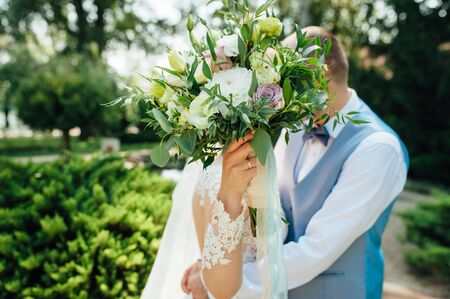 Cheerful newlyweds are hugging at their wedding and covering their face with a wedding bouquet. Photography and concept. 写真素材