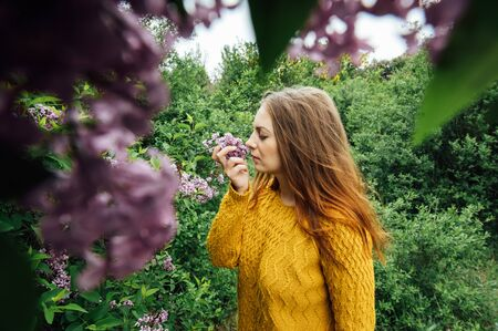 Outdoor fashion photo of beautiful young woman surrounded by flowers. Spring blossom