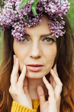 Beautiful woman with lilac flower wreath. Girl in a wreath of lilac in the spring.