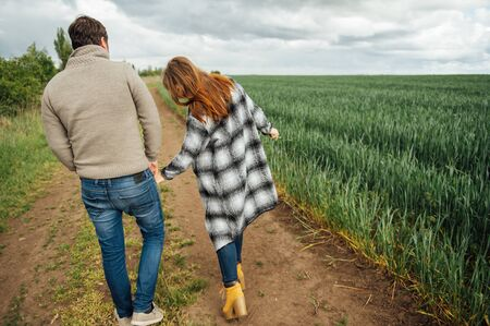 Young lovers walk near the field of early wheat. Hug and have fun