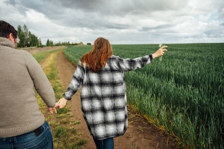 Young lovers walk near the field of early wheat. Hug and have fun. 免版税图像
