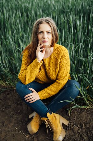 Beautiful girl with jeans, a yellow sweater and boots sits near an early wheat field