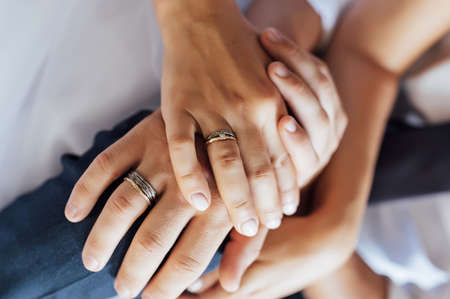 close-up portrait of the bride and groom. They hug their arms. Wedding rings on their hands