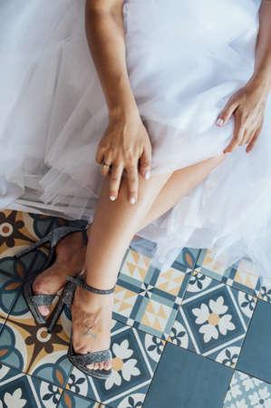 Bride in white wedding dress putting on silver shoes Standard-Bild