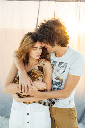 Romantic couple hugging with a cat. In the background is a gray cloth