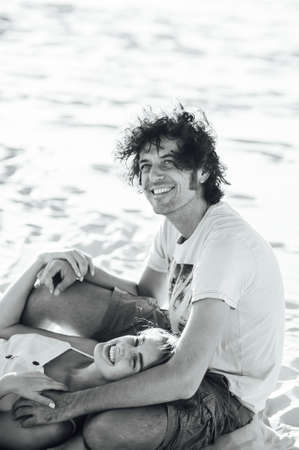 A curly-haired guy and a beautiful girl are having fun on the beach