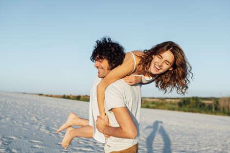 Beautiful couple having fun on the beach. Cheerful girl jumped on her boyfriends back