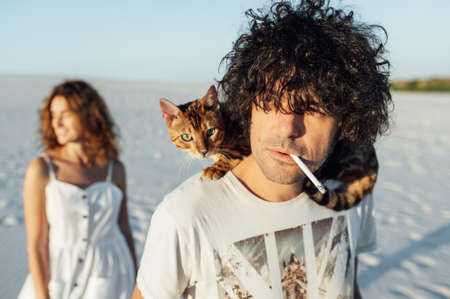 A guy with a cat on her neck smokes a cigarette. Girl standing in the background