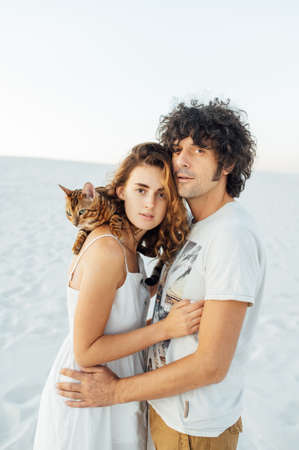 Beautiful couple of lovers hug each other and hold the cat in their arms