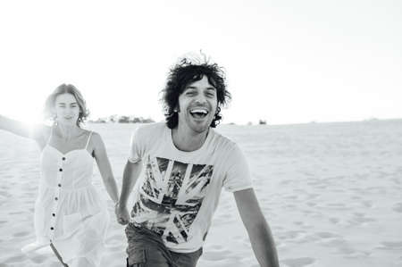 Cheerful couple in love running on the beach and enjoying their vacation