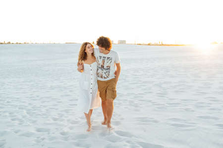 Vacation couple walking on beach together in love holding around each other.
