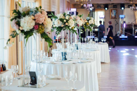 A beautiful vase of flowers on a table in a luxury restaurant. Wedding decorations
