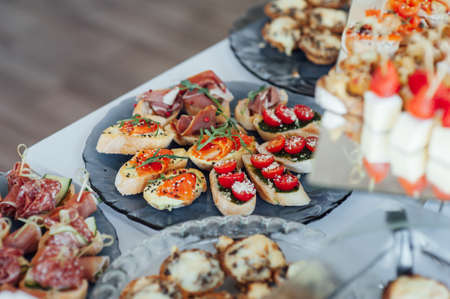 Sandwiches, canapes and cakes on the festive table. A wide variety of snacks Standard-Bild
