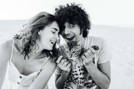 A handsome man with curly hair gently hugs his beloved. They have a cat in their hands