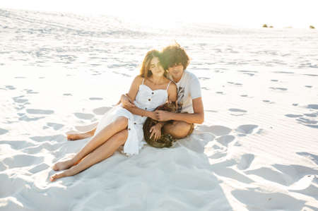 Cheerful young couple having fun on the beach with their bengal cat Standard-Bild