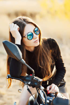 beautiful fashionable woman on a classic motorcycle, model appearance with sunglasses