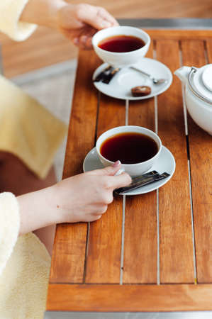 A loving couple sits in dressing gowns and drinks tea on a wooden table