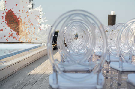 Glass chairs stand in a row in a beautiful wedding outing ceremony Standard-Bild