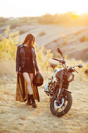beautiful girl biker in black clothes stands at the motorcycle with a safety helmet in his hands Standard-Bild