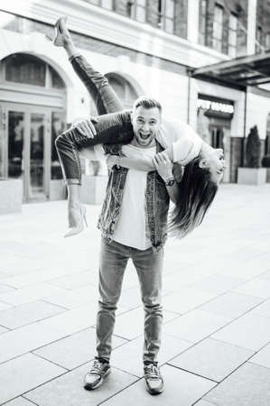 Fashion outdoor romantic portrait of beautiful young couple in love and hugs on the street.