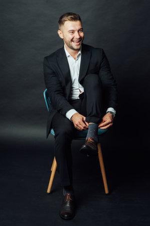 Handsome businessman man sitting on chair in photo studio