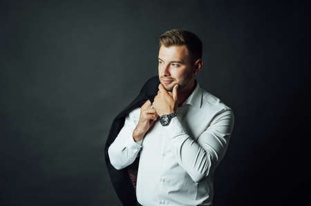 Handsome male businessman with suit posing in a photo studio. Half-length portrait